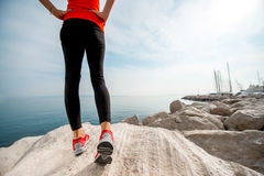 Sporty woman legs on the rocky beach Stock Image