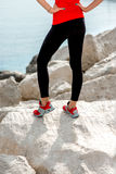 Sporty woman legs on the rocky beach stock photography