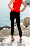 Sporty woman legs on the rocky beach royalty free stock photo
