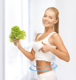 Sporty woman with lettuce showing abs Stock Image