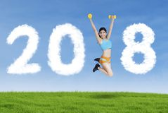 Sporty woman jumping with numbers 2018 Stock Photo
