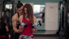 Sporty woman lifts dumbbells while training in a sport club. Athletic man is helping her to do the exercise correctly. stock video