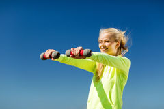 Sporty woman with light dumbbells outdoors Stock Photo