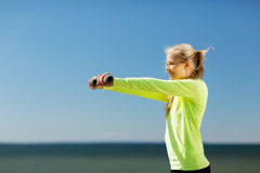 Sporty woman with light dumbbells outdoors Royalty Free Stock Photography