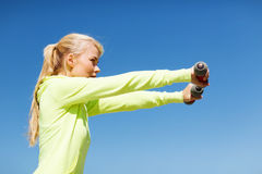 Sporty woman with light dumbbells outdoors Royalty Free Stock Photo