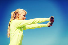 Sporty woman with light dumbbells outdoors Royalty Free Stock Images