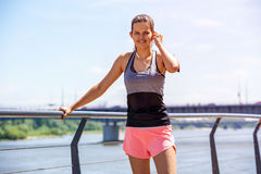 Sporty woman listening music before running. Female athlete list. Ening music while doing sport Stock Photo