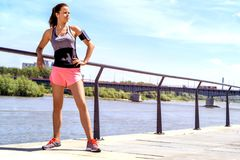 Sporty woman listening music before training outdoor. Female ath. Lete looking on side in city Stock Images
