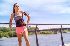 Sporty woman listening music before training outdoor. Female ath. Lete looking on side in city Royalty Free Stock Photo