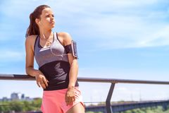 Sporty woman listening music before training outdoor. Female ath. Lete looking on side in city Stock Photos