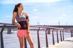 Sporty woman listening music before training outdoor. Female ath. Lete looking on side in city Stock Image