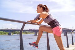 Sporty woman listening music before training outdoor. Female ath. Lete looking at river in city Royalty Free Stock Photography