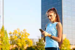 Sporty Woman listening to music with earphones. Young woman listening to music with earphones on smart phone app for fitness motivation. Athlete runner in Royalty Free Stock Images