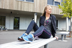 Sporty Woman Listening To Music While Sitting On Bench Stock Photos