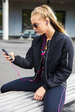 Sporty Woman Listening To Music While Sitting On Bench Stock Photo