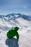 Sporty woman looking to snow mountains. Sporty woman on the top of peak looking to snow mountains Royalty Free Stock Photos