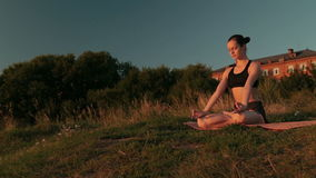 Sporty woman in lotus position in the park at sunset stock video