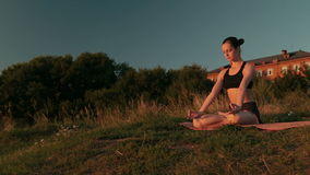 Sporty woman in lotus position in the park at sunset stock video footage