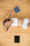Sporty woman lying next to a tablet and dumbbells Royalty Free Stock Photography