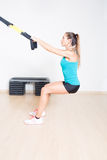 Sporty woman makes suspension training Royalty Free Stock Photography