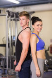 Sporty woman and man standing back to back in gym Royalty Free Stock Images