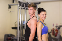 Sporty woman and man standing back to back in the gym Stock Image