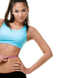 Sporty woman measures her waist. With  measuring tape, isolated on white Stock Photo