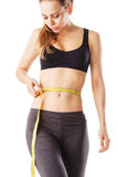 Sporty woman measuring her waist fitness with a tape measure. Isolated on white Royalty Free Stock Photos