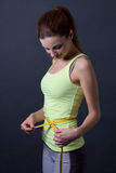 Sporty woman measuring her waist over grey Stock Photo