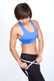 Sporty woman with measuring tape around hip. Stock Image