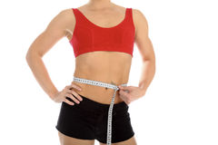 Sporty woman with a measuring tape round the waist Stock Photo