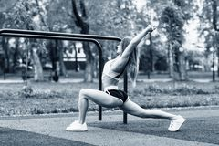 Sporty woman with perfect athletic body stretching in the park. royalty free stock photography