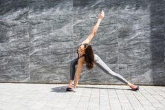 Fitness sport girl in fashion sportswear doing yoga fitness exercise in the street, outdoor sports, urban style royalty free stock photography