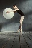 Sporty woman performing using the white balloon Stock Images