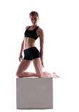 Sporty woman posing with cube looking at camera Royalty Free Stock Photography