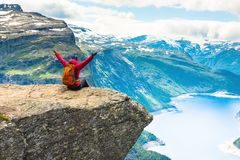 Sporty woman posing on Trolltunga Norway. Sporty woman posing on Trolltunga. Happy hiker enjoy beautiful lake and good weather in Norway Royalty Free Stock Photos