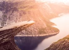 Sporty woman posing on Trolltunga Norway. Sporty woman posing on Trolltunga. Happy hiker enjoy beautiful lake and good weather in Norway Royalty Free Stock Photo