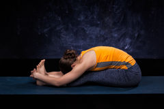 Sporty woman practices Ashtanga Vinyasa yoga asana. Sporty fit woman practices Ashtanga Vinyasa yoga back bending asana Paschimottanasana - seated forward bend royalty free stock photo