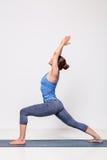 Sporty woman practices yoga Warrior pose asana Royalty Free Stock Photo