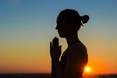 Sporty woman practicing yoga at sunset, making hand greeting namaste Stock Photography
