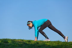 Sporty woman preparing to run royalty free stock image