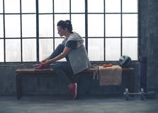 Sporty woman in profile sitting on bench tying shoe in loft gym Stock Image