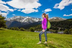 Side of woman on meadow looking at snowy mountain ready to hike stock photo