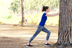 Sporty woman pushing against tree Stock Images
