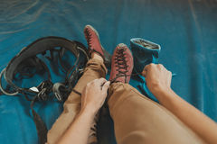 Sporty woman putting on climbing shoes Royalty Free Stock Image