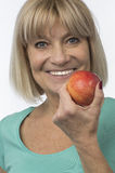 Sporty woman with a red apple senior Royalty Free Stock Images