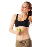 Sporty woman relaxed after workout holding green apple. Isolated on white Royalty Free Stock Photo