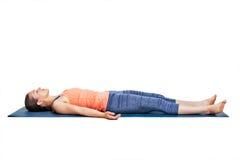 Sporty woman relaxes in yoga asana Savasana Stock Photography