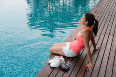 Sporty woman relaxing at poolside Royalty Free Stock Images