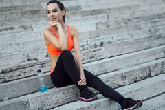 Sporty woman relaxing on stairs royalty free stock photography